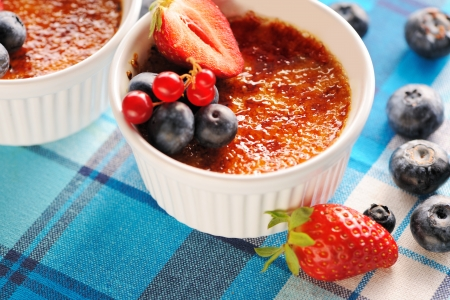 french cuisine: Creme brulee (cream brulee, burnt cream) with fruits and berries