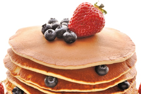 Delicious freshly prepared pancakes with strawberry and blueberries isolated on white photo