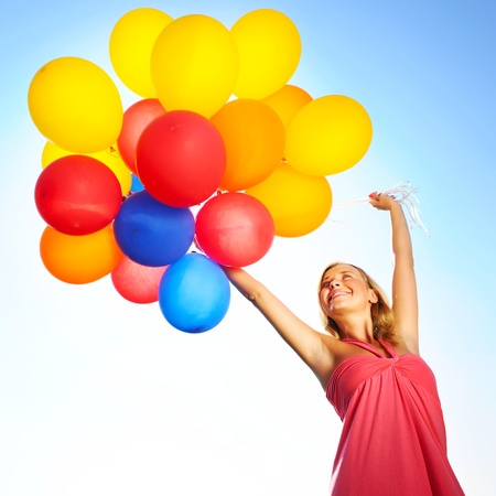 Woman holding balloons against sun and sky photo