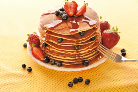 Delicious freshly prepared pancakes with strawberry and blueberries photo