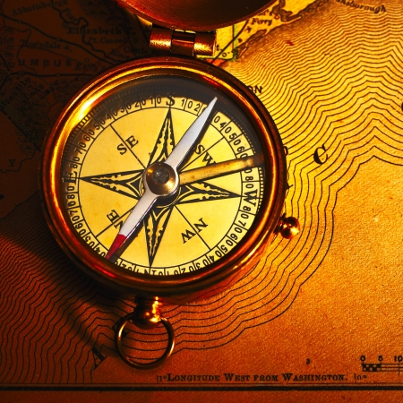 Antique brass compass over old paper background photo