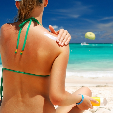 Tan woman applying sun protection lotion photo