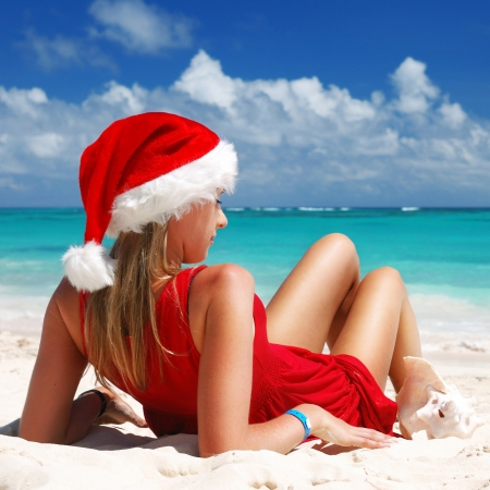 Woman on the beach in santa's hat photo