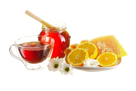Jar of honey and tea cup isolated over white photo