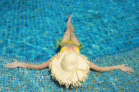 bikini pool: Girl with hat at tropical swimming pool Stock Photo