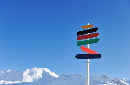 direction board: Arrow sign at mountains with snow in winter, Val-dIsere, Alps, France Stock Photo