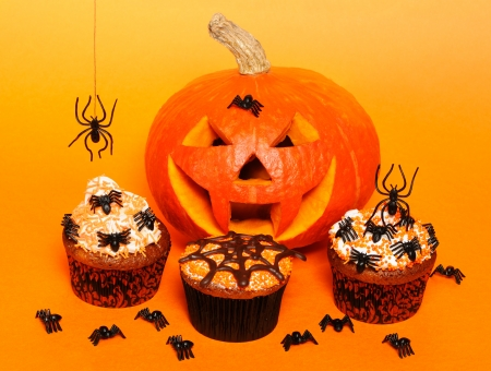 Halloween cupcakes with decoration over orange background photo