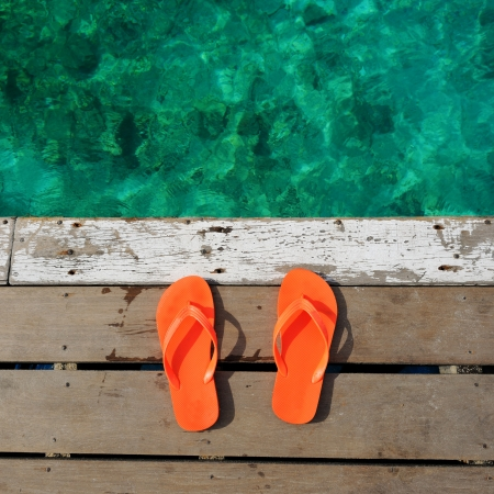 Sandals at jetty by the sea photo