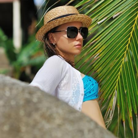 Woman in sunglasses near palm tree wearing hat