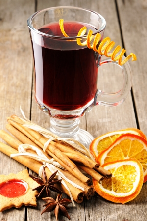 spiced: Glass of red mulled wine on wooden table