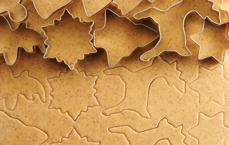 Christmas cookie cutters over homemade gingerbread dough photo