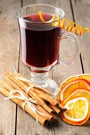 grog: Glass of red mulled wine on wooden table