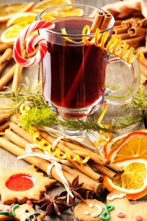 Glass of red mulled wine on wooden table photo