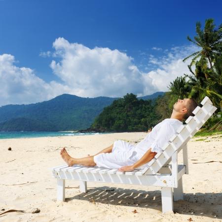 El hombre de blanco se relaja en una playa tropical Foto de archivo - 16352870