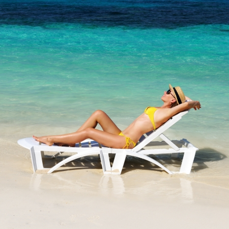 girl sit: Girl on a tropical beach with hat Stock Photo