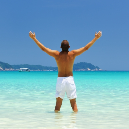 outstretch: Man in white at tropical beach Stock Photo