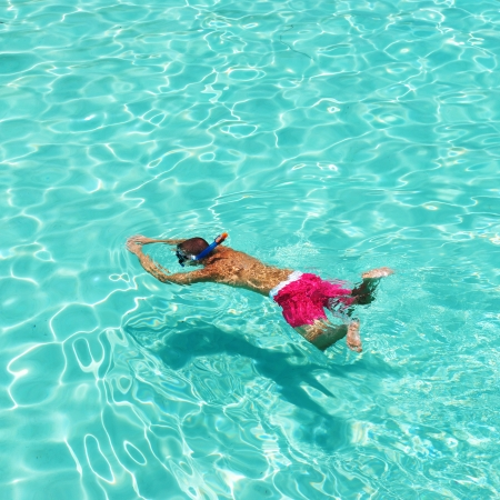 Man snorkeling in crystal clear turquoise water at tropical beach photo