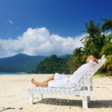 man in chair: Man in white relaxing on a tropical beach
