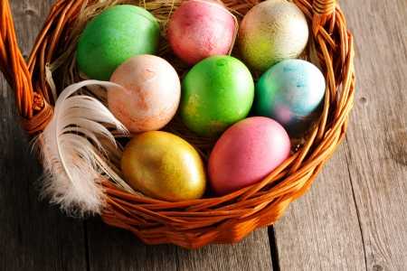 Colored easter eggs in basket on wooden table Stock Photo - 17303164