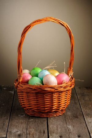 Colored easter eggs in basket on wooden table Stock Photo - 17303071