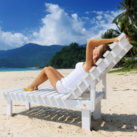 Girl on a tropical beach sitting at chaise lounge Stock Photo - 17302946