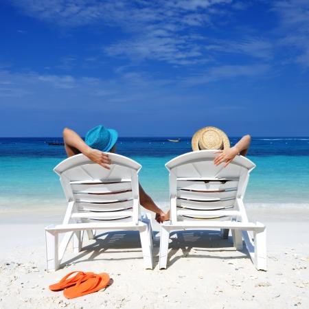 donna seduta sedia: Coppia su una spiaggia tropicale Archivio Fotografico