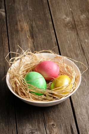 easter nest: Colored easter eggs in nest on wooden table Stock Photo