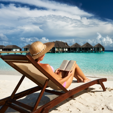 lounge chair: Young woman reading a book at the beach Editorial