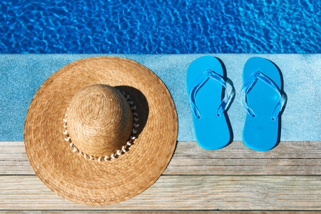 swimming shoes: Blue slippers and hat by a swimming pool