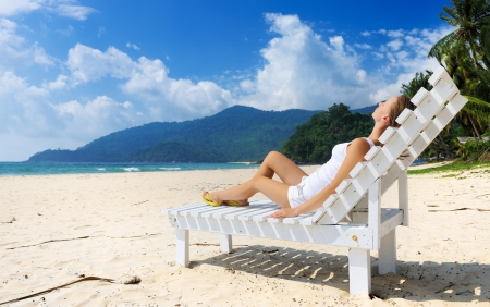 chaise lounge: Girl on a tropical beach sitting at chaise lounge