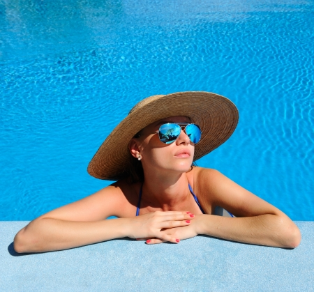 Woman in hat relaxing at the pool  Stock Photo - 18424029