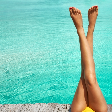 sexy legs: Womans legs at beach jetty Stock Photo