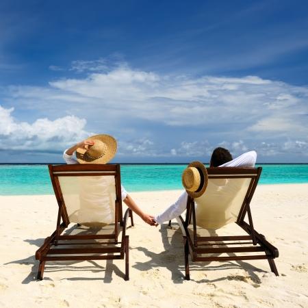 strandstoel: Paar op een tropisch strand op de Malediven Stockfoto