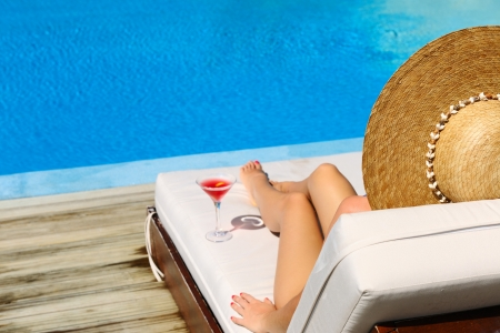 Woman in hat relaxing at the poolside with cosmopolitan cocktail Stock Photo