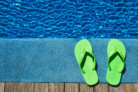 Green slippers by a swimming pool  photo