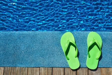 Groene slippers door een zwembad Stockfoto