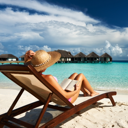 sunhat: Young woman reading a book at the beach Stock Photo