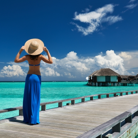 docks: Woman on a tropical beach jetty at Maldives Editorial
