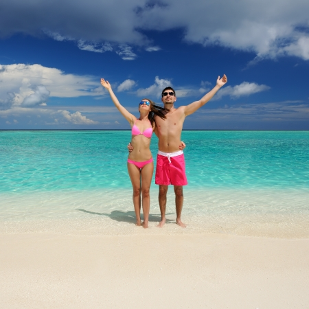 arms  outstretched: Couple on a tropical beach at Maldives