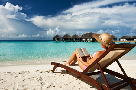 Young woman reading a book at the beach photo