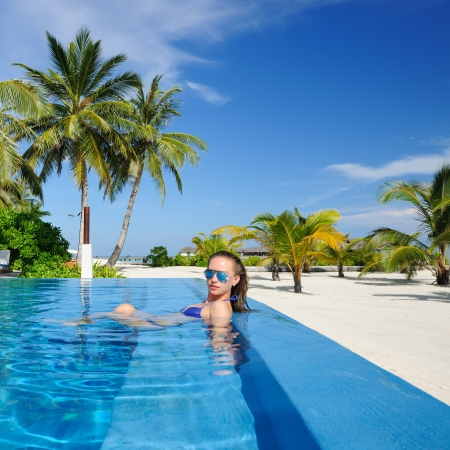 Woman in hat relaxing at the pool Stock Photo - 19001514