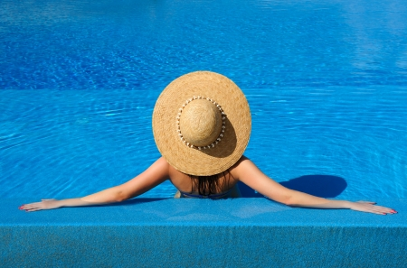 Woman in hat relaxing at the pool Stock Photo - 19144408