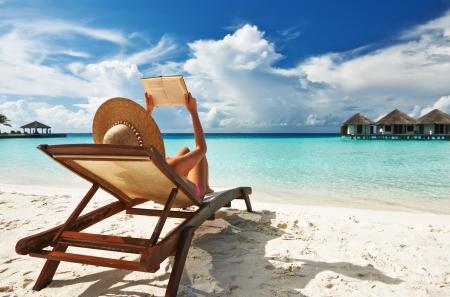 strandstoel: Jonge vrouw leest een boek op het strand Stockfoto