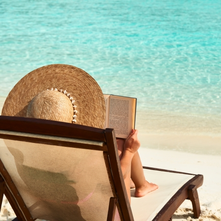 holiday summer: Young woman reading a book at the beach Stock Photo
