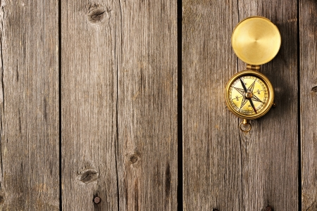 Antique brass compass over wooden background Stock Photo - 19135548