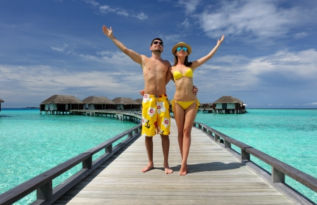 arms  outstretched: Couple on a tropical beach jetty at Maldives Editorial