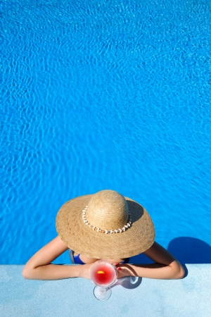 Woman in hat relaxing at the pool with cosmopolitan cocktail photo