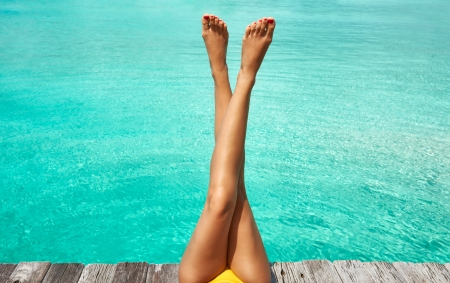 sexy beine: Beine einer Frau am Strand Steg Lizenzfreie Bilder