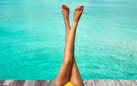 piernas sexys: Piernas de la mujer en la playa embarcadero