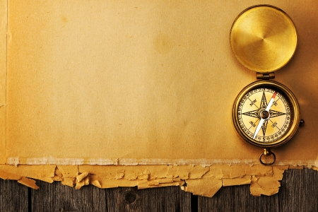 Antique brass compass over old paper background Stock Photo - 19358829